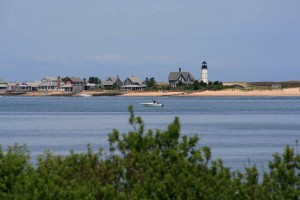 wide swarth of blue ocean against a backdrop of the sand, cottages, and lighthouse of Barnstable Harbor
