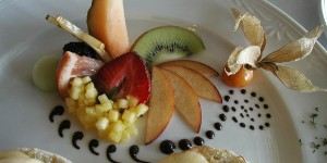 Fresh fruit garnish of melon, apples, kiwi, strawberries, and diced pineable on a white breakfast plate.